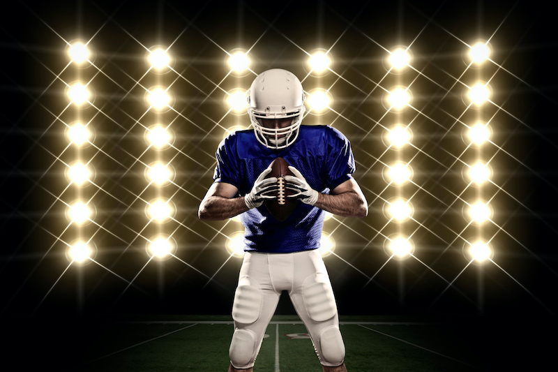 Image of a Football Quarterback in Lights holding the Ball