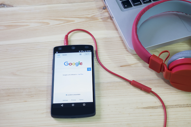 Cell phone sitting on a desk with headphone cable plugged in showing the Google search bar
