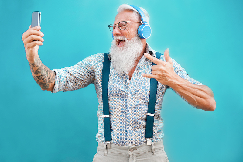 A elderly man with a beard and headphones taking a selfie into his smartphone.